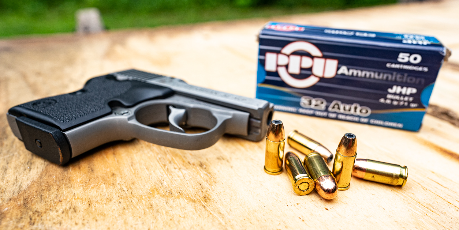 32 ACP ammo and pistol on a shooting bench