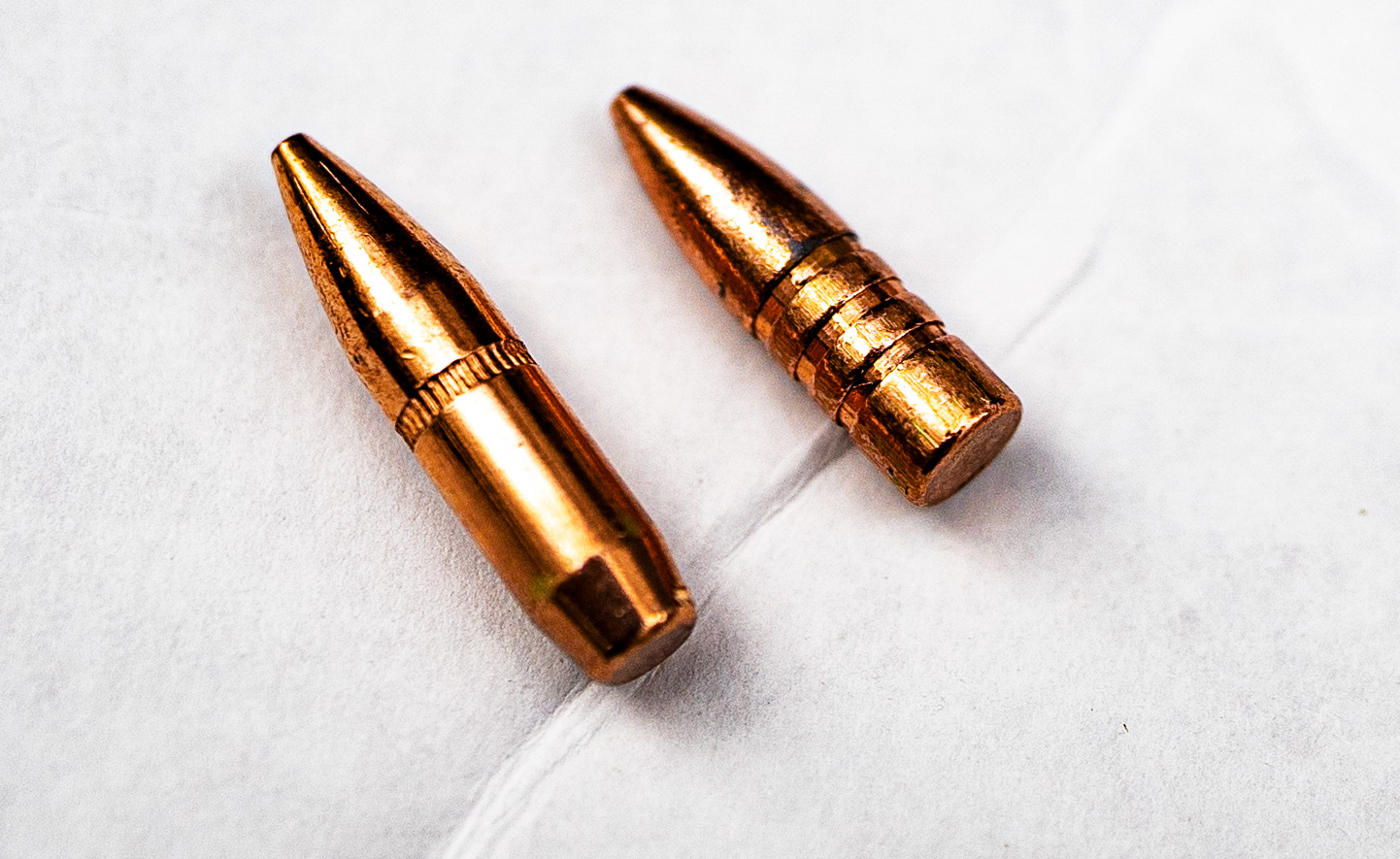 A boat tail bullet side by side with a flat base bullet