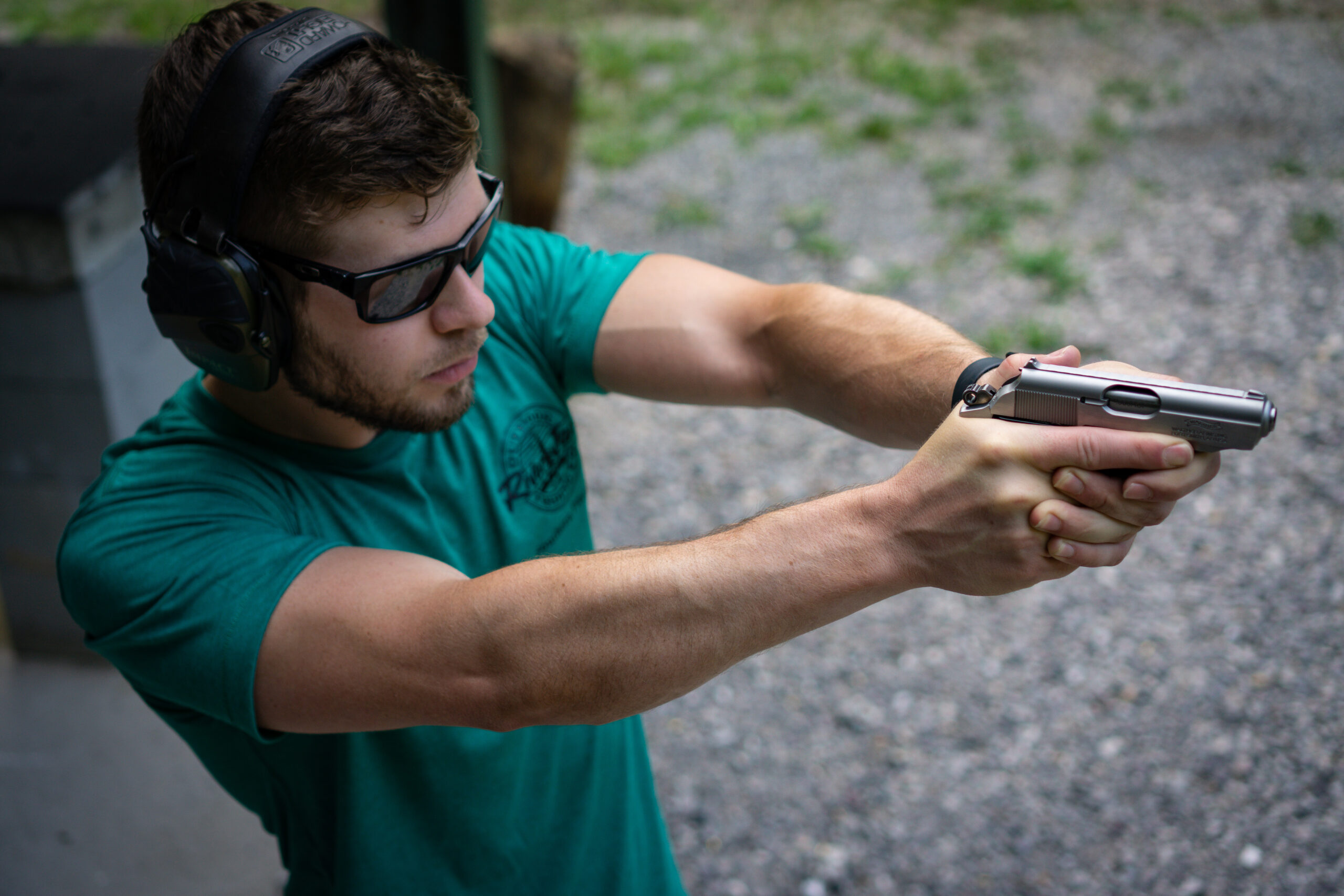 The author firing the Walther PPK pistol at a shooting range as part of the testing done in this review.