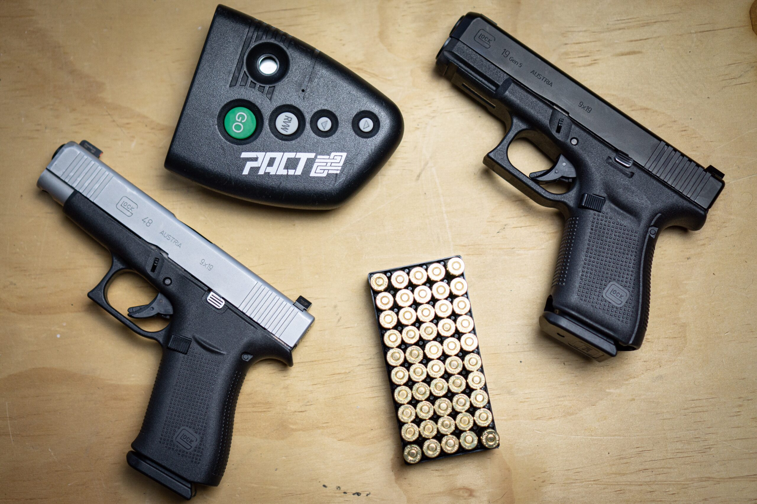 Glock 48 And Glock 19 with shot timer and ammo on a table