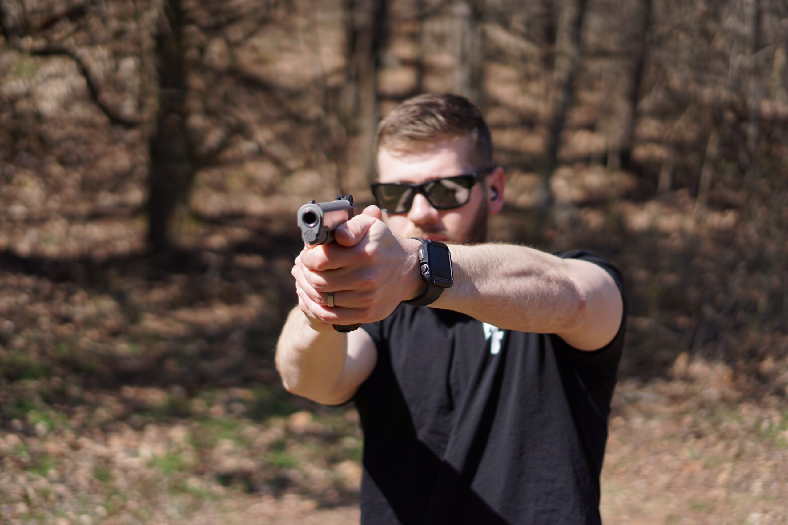 The Author firing a Dan Wesson 1911 Classic pistol at a shooting range