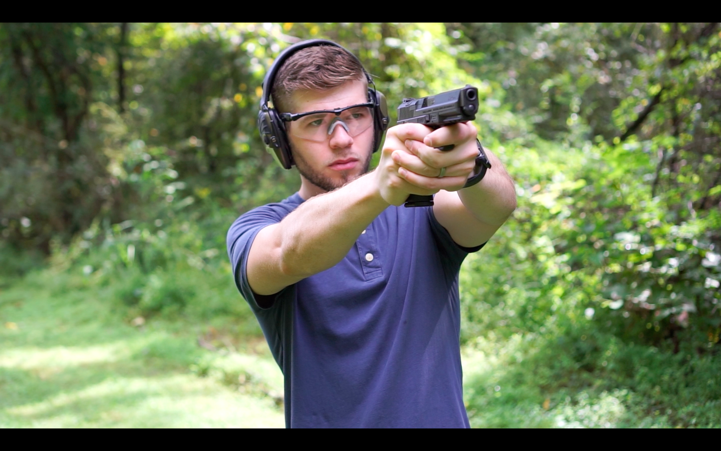 The author Firing a Canik TP9 at the shooting range as part of his review