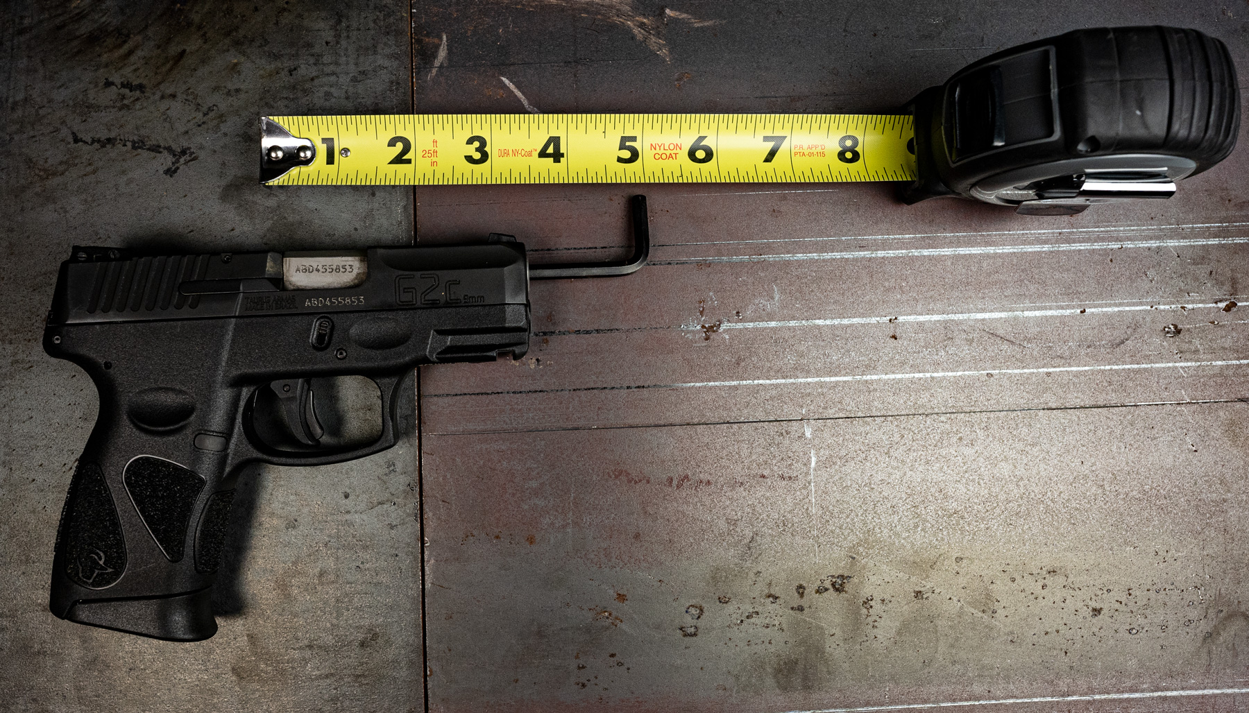 A dowel and tape measure showing how to measure the length of a barrel with a pistol on a table